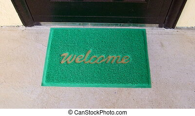Welcome home mat female traveler with suitcase passes through the front door