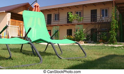Sun loungers on grass meadow of small tourist hotel - Sun...
