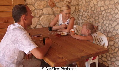 Family eating in outdoor summer kitchen in the garden