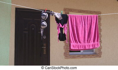 Female swimsuit and beach towel drying on clothesline in...