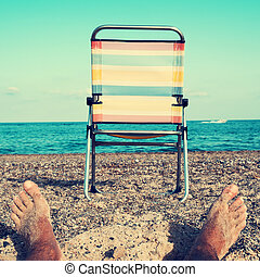 chair and young man on the beach, filtered - closeup of the...