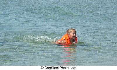 Little girl in inflatable life jacket learning to swim on beach vacation