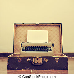 old typewriter in an old suitcase, with a retro effect - an...