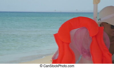 Young woman sitting in shade of umbrella on sandy beach...