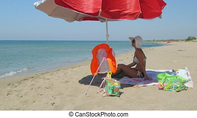 Young woman sitting in shade of umbrella on sandy beach eating peach