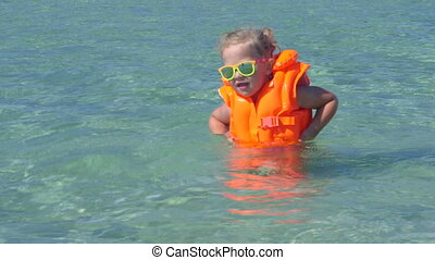 Cute little girl wearing life jacket in turquoise water on...
