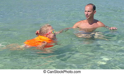 Father with little daughter wearing inflatable life jacket learning to swim