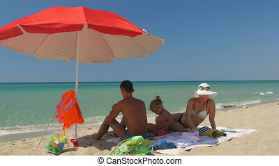 Family on sand beach in shade of red umbrella against turquoise sea and blue sky