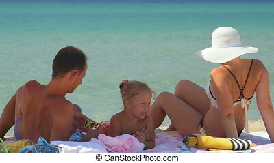 Young family with little daughter enjoying summer vacation on sandy beach