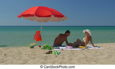 Young family enjoying summer vacation on sandy beach  beside turquoise sea water