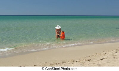 Mother and little daughter in lifejacket on sandy beach walking to swim in sea