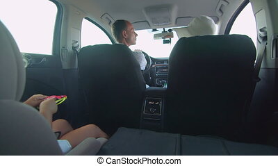 Young family with little girl in child back seat traveling by car