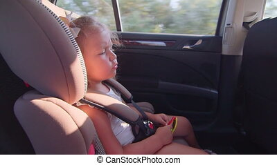 Little girl traveling with family by car singing road trip...