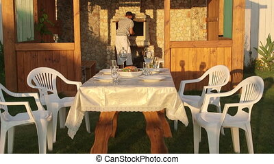 Young family serving dining table in garden near outdoor stone fireplace