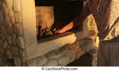 Man lights the fire in outdoor natural stone fireplace at...