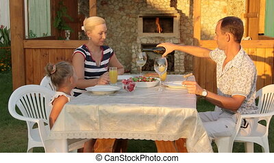 Young family with child dining in the backyard beside outdoor fireplace