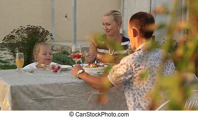 Summer evening in backyard young family with his little daughter enjoying dinner