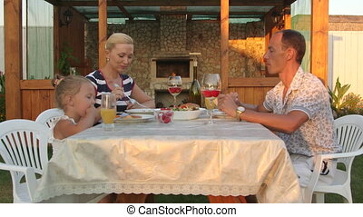 Young family with child dining in the backyard beside...