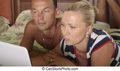Adult couple using laptop something discussing lying on bed in bedroom