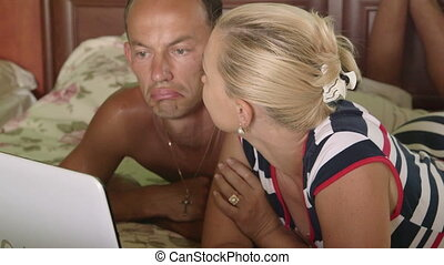 Adult couple smiling while looking at laptop monitor in bedroom