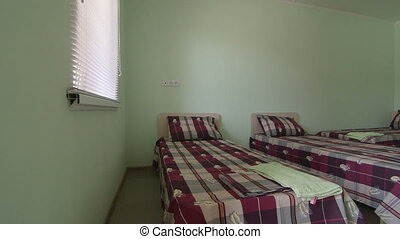 Cheap budget hotel room interior with three beds pan shot