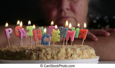 Senior woman contemplating birthday cake with candles Happy Birthday in Russian