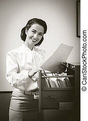Smiling secretary searching files in the filing cabinet -...