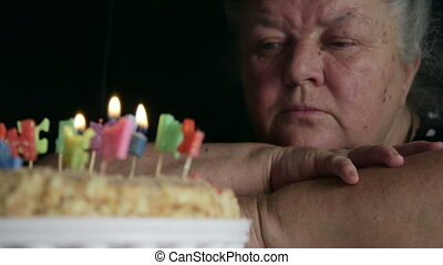 Sad senior woman looking at birthday cake with letter...
