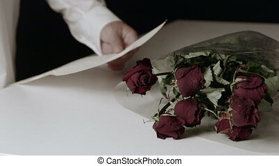 Man reading farewell letter with bouquet of withered roses on table