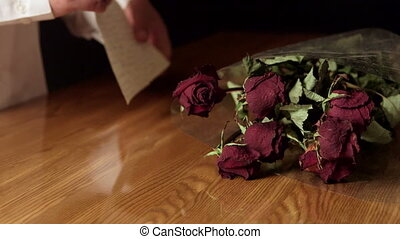 Man reading goodbye letter with red dried rose bouquet on wooden table