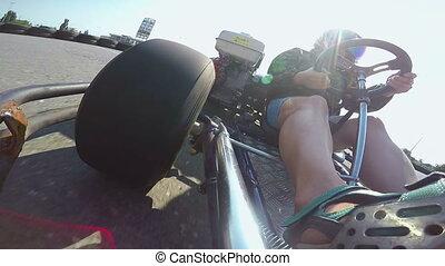 Karting female driver in helmet rushes go-kart on kart track...