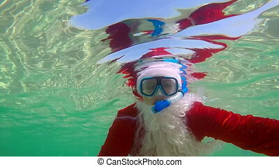 Slow motion Santa Claus snorkeling underwater on tropical...