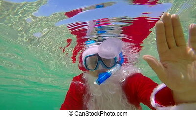 Diver dressed as Santa Claus on Christmas day waving hand under water
