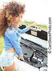 Girl inspecting her car