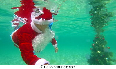 Scuba with Santa Claus beside Christmas tree under water