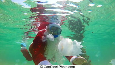 Scuba Santa Claus beside Christmas tree under water waving hand welcoming