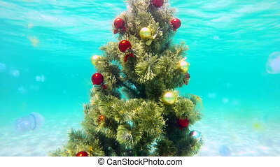 Festive Christmas tree installed on sand seabed underwater
