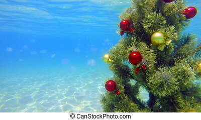 Under water decorated Christmas tree sparkling in turquoise...