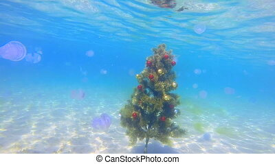 Festive Christmas tree installed on sand seabed under water