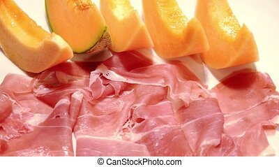 dry cured ham and melon on white background