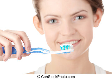 Young girl brushing her teeth happily, isolated