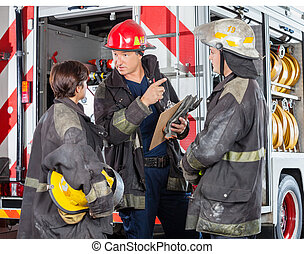 Firefighter Discussing With Colleagues At Fire Station -...