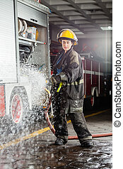 Confident Firewoman Spraying Water During Practice -...