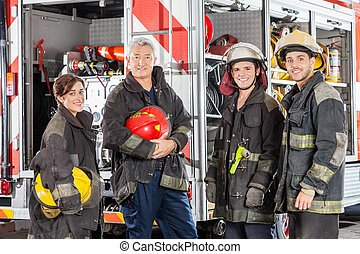 Happy Team Of Firefighters Against Truck - Happy team of...
