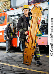 Portrait Of Confident Firefighter Holding Wooden Stretcher -...