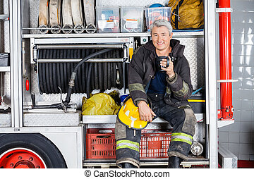 Happy Fireman Sitting In Truck At Fire Station - Portrait of...