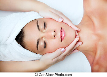 Beautiful young woman receiving facial massage. Top view.