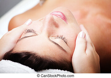 Beautiful young woman receiving facial massage - Close-up of...