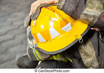 Firefighter Holding Yellow Helmet At Fire Station - Cropped...