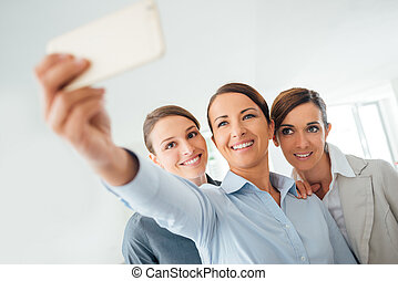 Smiling business women team taking a selfie - Smiling...